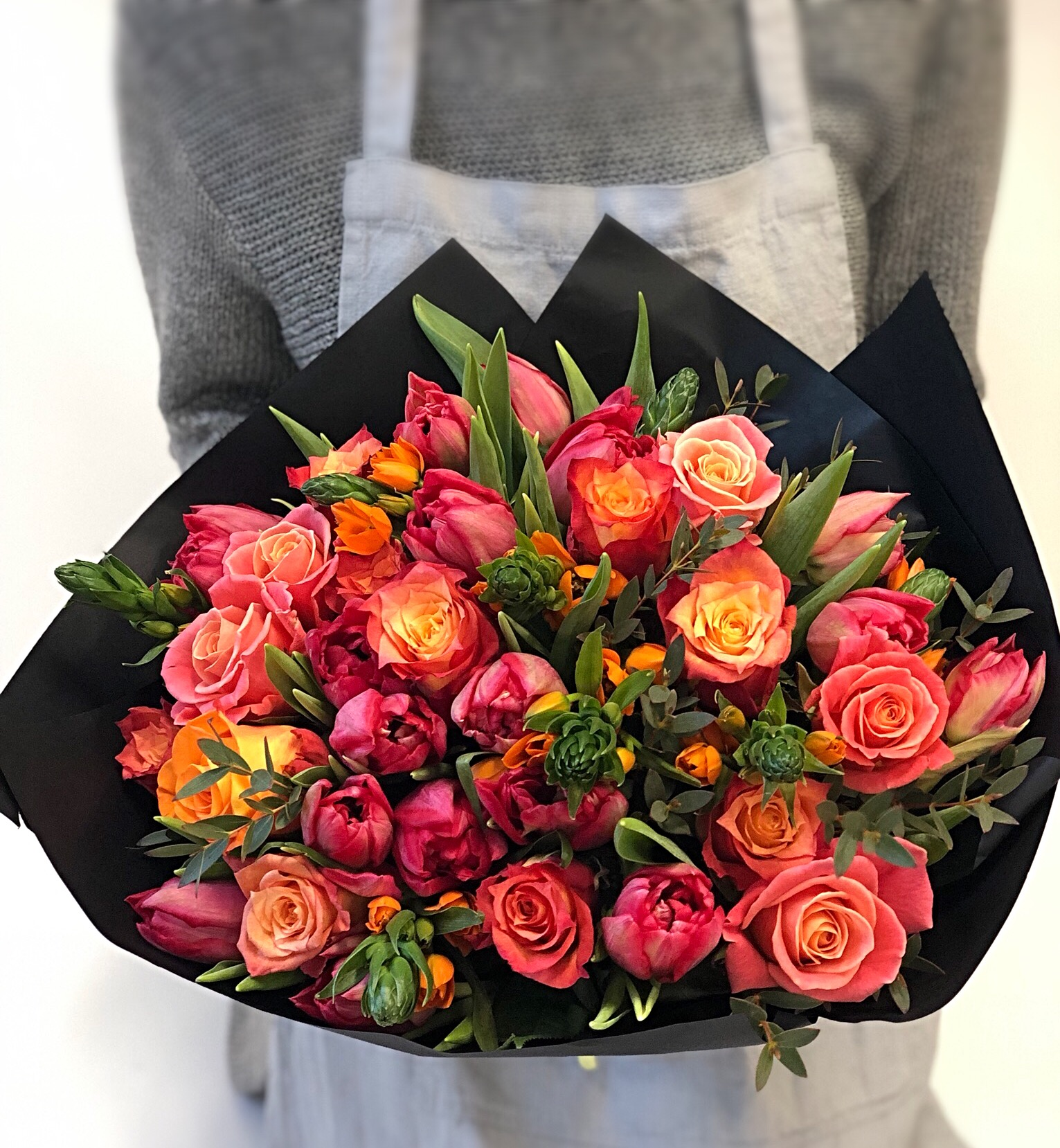 Orange and red flower bouquet wrapped in black paper